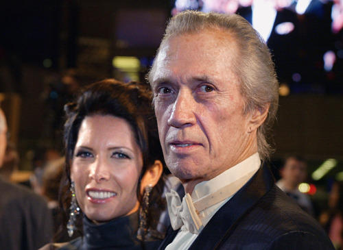"David Carradine and his wife pose as they arrive at the palais des festivals to attend the screening of ""Ghosts of the Abyss""."