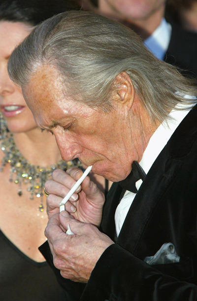 "Actor David Carradine lights a cigarette as he arrives at the screening of ""Le Temps Du Loup""."