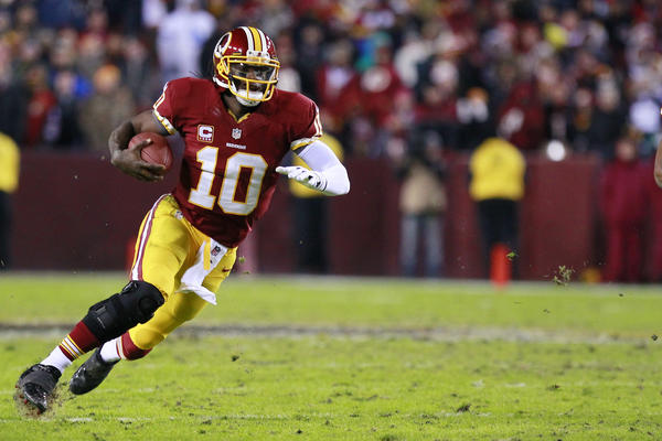 Redskins quarterback Robert Griffin III runs with the ball against the Dallas Cowboys. Washington beat Dallas to win the NFC East and will play the Seahawks in the first round.