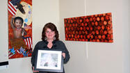 "Penelope Wilson, of Hollidaysburg holds ""Double Dip"", a graphite drawing depicting a favorite Hollidaysburg, Pa. sledding hill. She is framed by her artwork. At left is ""Celebration"" and at right, ""Adinkra."""