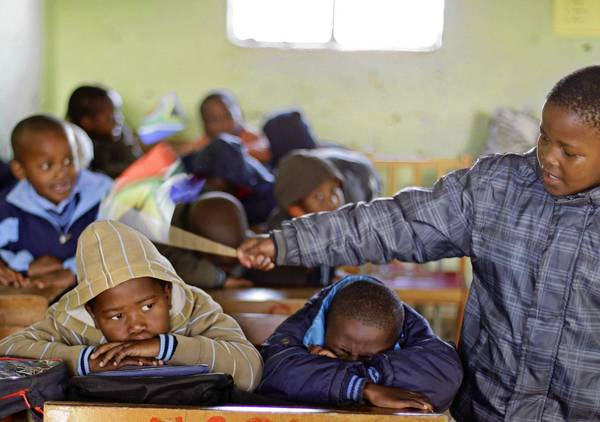 A boy keeps control over fellow students by tapping them with a South African flag at a school in Qunu.
