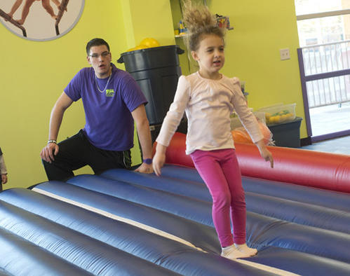 "Instructor Scott Tocci watches as Breanna Good, 5, of Stewartsville, New Jersey, leaps during an excersize in the""Mini Jacks"" sports class at the Little Gym in Bethlehem Township on Thursday. The class meet every Thursday at 1 pm, helping kids learn motor skills through sports and play."
