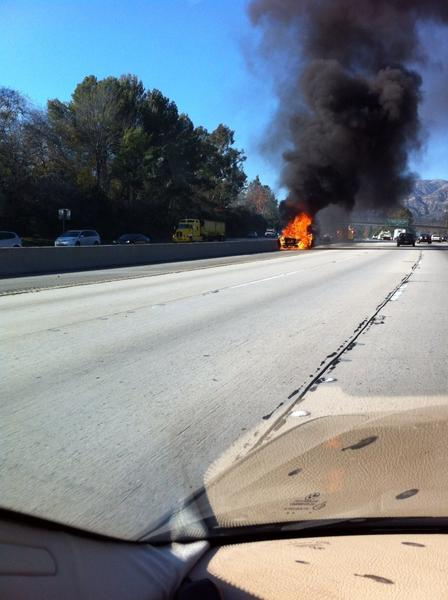 A man was arrested on suspicion of driving under the influence Thursday after his car hit the center divider on the westbound 210 Freeway in La Canada and burst into flames.