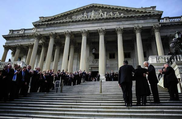 Vice President Joe Biden, right, helps Sen. Mark Steven Kirk (R-Ill.) climb the Capitol stairs for the first day of the 113th Congress. Kirk is recovering from a stroke that sidelined him for nearly a year.