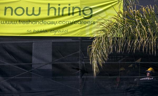 The job market maintained its modest growth in December, thanks partly to a pickup in construction activity. Above, a worker at a new site for a future Fresh & Easy supermarket in Los Angeles.