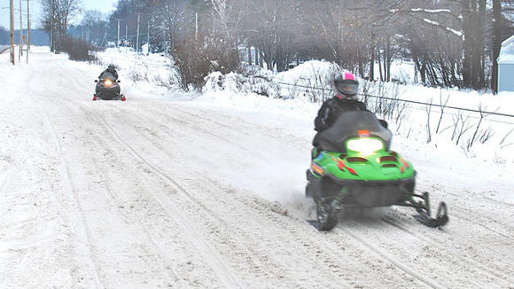 THESE TWO SNOWMOBILERS were enjoying the holiday break riding the trail along Old 27 next to Otsego Lake on Monday morning.