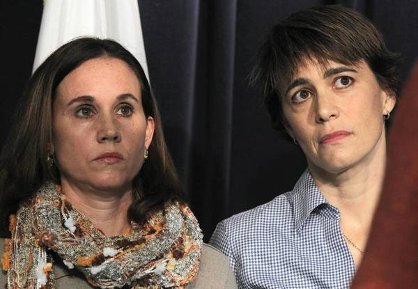 Ill. Rep. Deb Mell, right, and her wife, Christin Baker, left, watch as marriage equality advocates urge supporters across Illinois to make their voices heard on Illinois' marriage equality bill, during a press conference at the Thompson Center. Mell and Baker were married in Iowa in 2011.