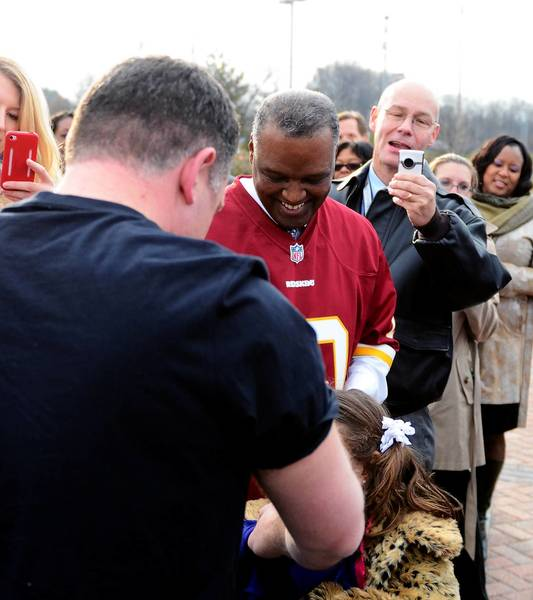 Mark Miller, head of the county goverment's Office of Public Information, takes a picture of County Executive Ken Ulman last month as Ulman makes good on his Ravens-Redskins wager with Prince George's County Executive Rushern Baker III, center.