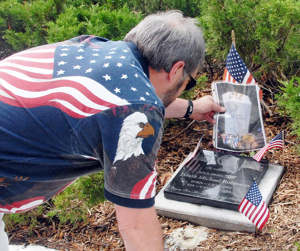 Dan Robinson, of Petoskey, father of fallen soldier and Navy SEAL Heath Robinson, places a laminated photo of his son's headstone at Arlington National Cemetery on Heath's plaque in Petoskey's Pennsylvania Park, during the Petoskey Memorial Day services.