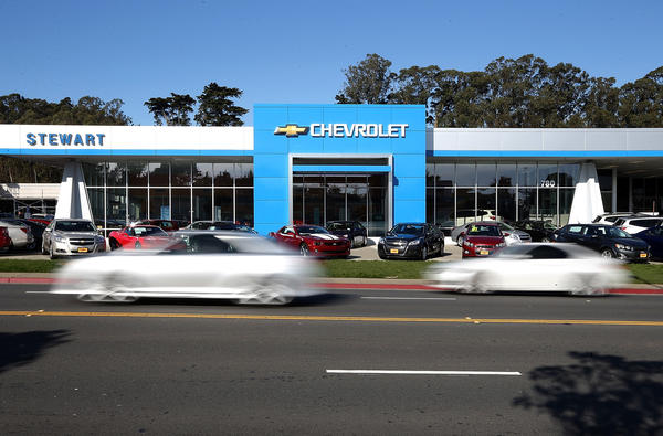 Cars drive by a Chevrolet dealership on Jan. 3. Chrylser and General Motors led automakers in the best sales year since 2007. Chrysler's December sales jumped 10% while GM's was up 4.9%.