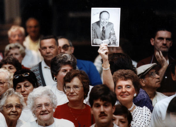 "MANCHESTER 7/13/91 - Ruth Aronson of West Hartford holds an old photograph of Bob Steele over her head while she and hundreds of other Bob Steele fans watched his birthday broadcast at the Buckland Hills mall. ""I've been in love with him since I was then years old,"" said Aronson."