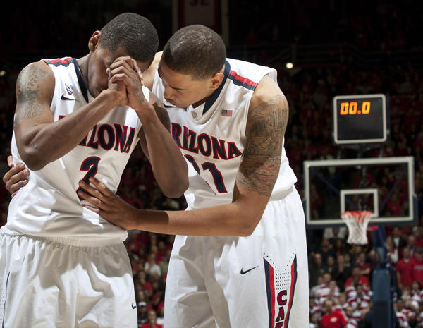 Arizona Wildcats guard Mark Lyons (L) and forward Brandon Ashley (R) wait for the officials to announce if the Colorado Buffaloes last shot went off before the buzzer at the end of regulation. Officials ruled it did not after originally calling the shot good, even though replay evidence was inconclusive.