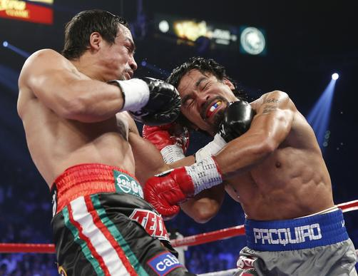 Juan Manuel Marquez and Manny Pacquiao trade punches during their WBO welterweight fight at the MGM Grand Garden Arena in Las Vegas.