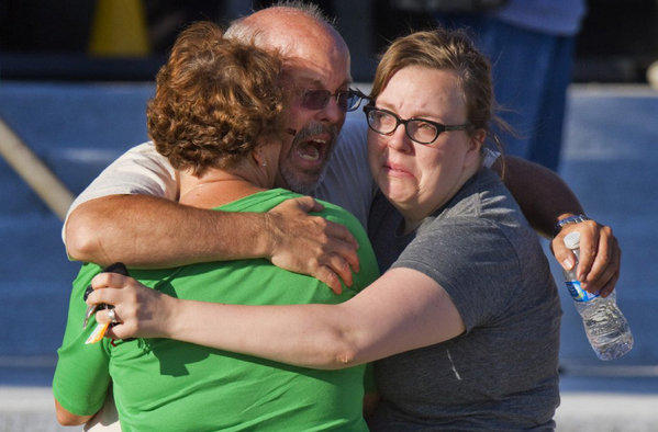 "After the July shooting, Tom Sullivan, center, embraces family members outside Gateway High School where he had been searching for his son, Alex Sullivan, who celebrated his 27th birthday by going to see ""The Dark Knight Rises"" at a movie theater where a gunman opened fire, in Aurora, Colo."