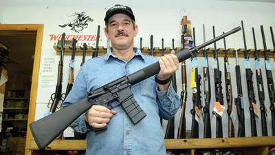 "Walter Mort, a clerk at Hoover's Outfitting in Rockwood holds a Bushmaster AR 15 semi automatic rifle equipped with a 30 round clip, bayonet lug and a flash suppressor. Mort said that business: ""picked up a little after the election, but went up instantly as soon as the President and the Republicans made their announcements. Especially anything high capacity-- hand guns and black rifles and tactical type weapons such as semi-automatic and military type guns."""