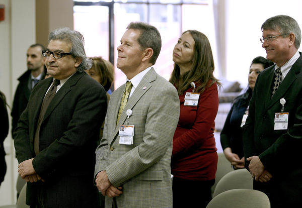 Attendees, including hospital President Jack Ivie, center, listen to His Eminence Archbishop Moushegh Mardirossian, Prelate of the Armenian Church of the Western United States, speak during blessing of the water at Glendale Memorial Hospital in Glendale on Friday, January 4, 2013. His Eminence Mardirossian performed a short ceremony to celebrate New Years and the Armenian Christmas this weekend.