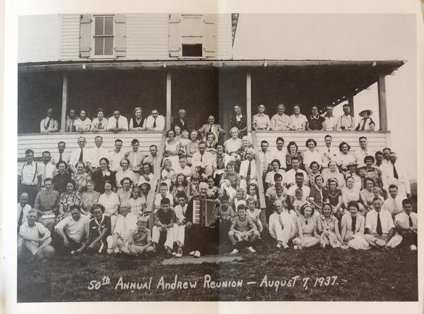 A photograph of the Andrew family's 50th Annual Reunion folds out of a book on family history.  They are pictured in front of their rebuilt summer home on Andrew Mountain in Naugatuck.  The first house burned down in 1925.  This home burned down in the 1950s and was never rebuilt.