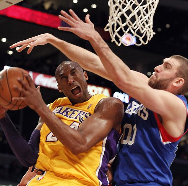 Kobe Bryant scores an acrobatic reverse layup around 76ers center Spence Hawes in the first half