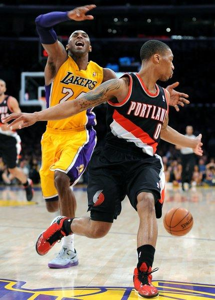 Kobe Bryant loses the ball against Trail Blazers guard Damian Lillard