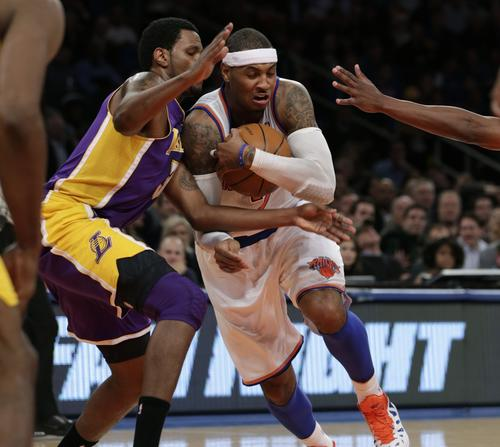 Carmelo Anthony protects the ball as he drives past Los Angeles Lakers forward Devin Ebanks.