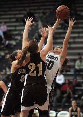Liberty #50 Maggie Zerbe, Whitehall #32 Nicole Umbenhauer and Whitehall #21 Brook Mellinger battle for the ball in their girls basketball game held at Liberty High School on Friday.