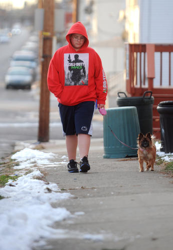 Jose Montecinos, 14, of Easton, walks his dog, Molly, 1, on Wednesday. Jose is wearing shorts despite the cold temperatures and says he's not cold.