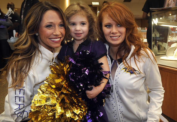 Three-year-old Amelia Albrecht of Parkville, center, poses with Ravens cheerleaders Dana, left, and Adriene, right, at a Ravens pep rally which was held at Smyth Jewelers in the Annapolis Towne Centre this morning.