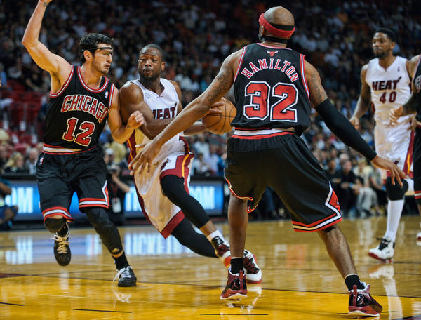 Miami Heat guard Dwyane Wade drives through the defense of Chicago Bulls Kirk Hinrich and Richard Hamilton during the first half of their game, Friday, January 4, 2013, at AmericanAirlines Arena.