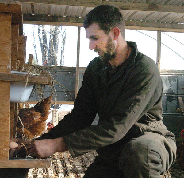 Will Meurer checks on the eggs his laying hens produced this week. Meurer has more than 300 chickens on his farm located on Combs Ferry Road in Clark County. Meurer discovered an interest in farming during the Governor's Scholars program at Eastern Kentucky University in 2004.