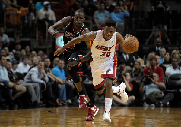 Miami Heat guard Norris Cole beats Chicago Bulls forward Luol Deng to the loose ball during the first half of their game, Friday, January 4, 2013, at AmericanAirlines Arena.