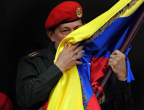 Venezuelan President Hugo Chavez kisses a Venezuelan national flag at Miraflores presidential palace in Caracas on July 4, 2011. Chavez had returned to Venezuela two days prior after spending three weeks in Cuba to have a cancerous tumor removed.