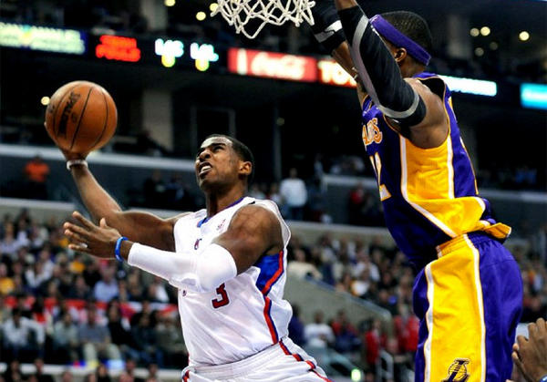 Clippers guard Chris Paul drives to the basket against Lakers' Dwight Howard.