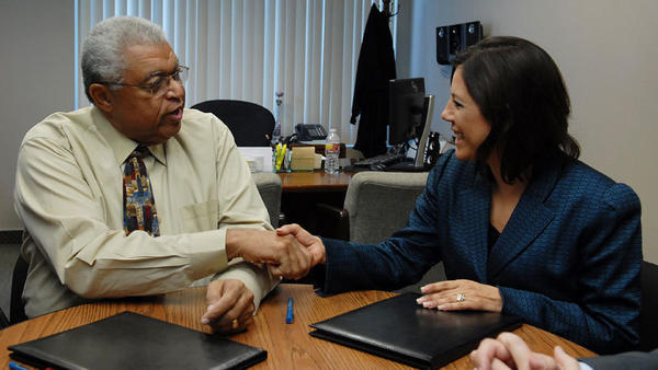 Calexico Chamber of Commerce President Carlton Hargrave shakes hands with Mexico Consul Gina Andrea Cruz Blackledge during a meeting Friday to sign papers partnering them on new health plans.