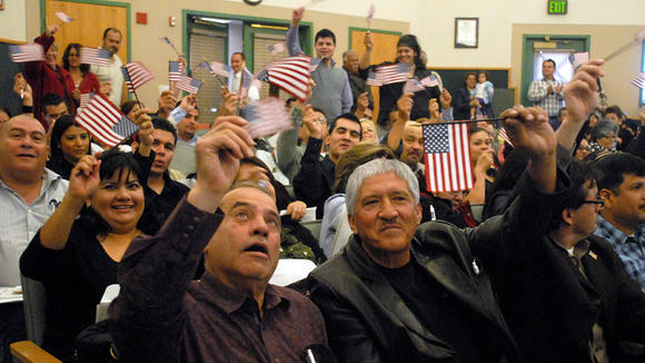 New United States citizens celebrate at the end of their citizenship ceremony.