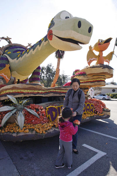 Lin Chen, top, gives a flower to her daughter, Eleni Koutsoukos, 4, after visiting the Dino-Soar float at Memorial Park in La Canada on Saturday, January 5, 2013.