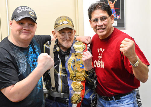 Pro Wrestling Hall of famer Tito Santana, right, poses for a photo with fans Todd Blawn of Allentown and his father James Blawn of Allentown. Santana was in Allentown at Merchant's Square to sign autographs for his fans.