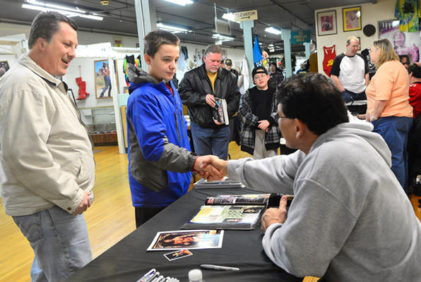 Pro Wrestling Hall of famer Tito Santana, right, shakes hands with fans Greg Kish of Emmaus, left, and Jared Kish, 11, his son, center. Santana was in Allentown at Merchant's Square to sign autographs for his fans.