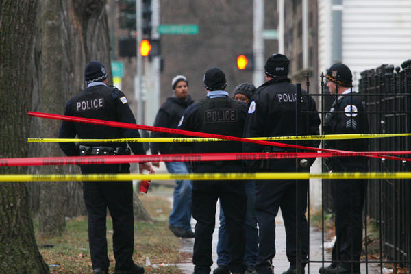 Chicago police gather at the scene of a fatal shooting near 55th Street and Loomis Avenue.