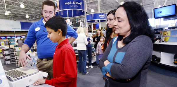 Best Buy employee DJ Johnson, left, shows Shahzeb Ahmed, 12, sister Shahroz Fatima and mother Tasneem Ahmed a computer on his shopping spree on Saturday as part of being a Make-A-Wish recipient.
