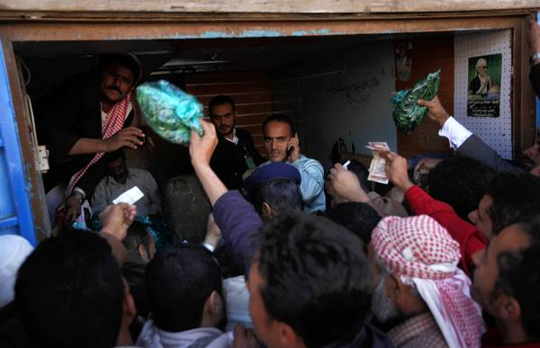 Yemeni men gather to buy khat in Sana. The narcotic plant offers ritual and repose in the desert country but is arousing growing opposition.