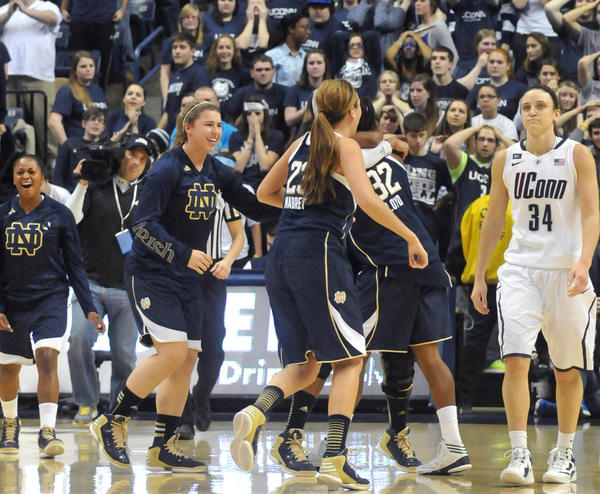 UConn's Kelly Faris, right, returns to the bench as Notre Dame players celebrate their victory at Gampel Pavilion Saturday afternoon.