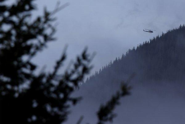 A King County Sheriff's Office helicopter flies over rugged terrain around Mount Si near North Bend, Wash., where searchers were looking for missing skydiver Kurt Ruppert of Florida.