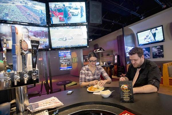 Floor manager Kristin Grassi takes a break with co-owner Matthew Cochran inside the new sports pub Rivals, located near Center Square in Easton.