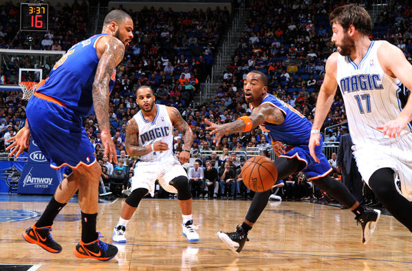 Orlando guard Jameer Nelson (14) passes inside to forward Josh McRoberts (17) between New York defenders Tyson Chandler (6) and J.R. Smith (8) during the first half of the Magic's game against the  Knicks in Orlando, Fla