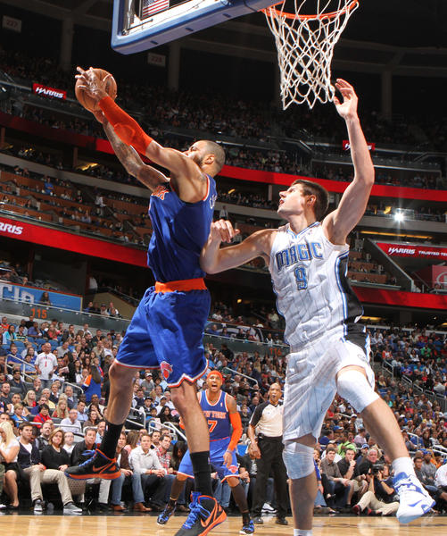 New York center Tyson Chandler (6) grabs a rebound over Orlando center Nikola Vucevic (9) during the second half of the Knicks 114-106 victory over the Magic in Orlando, Fla.