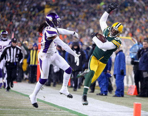 Packers wide receiver Greg Jennings gets pushed out of bounds by Vikings safety Mistral Raymond following a 32-yard pass play.