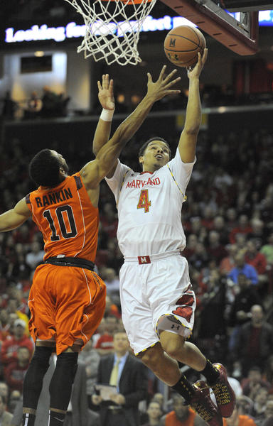Terrapin Seth Allen scores a basket as he gets around the Hokies' Marquis Rankin in the first half. The University of Maryland men's basketball team topped Virginia Tech Hokies at the Comcast Center, 94-71.