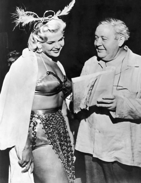 "English-American veteran actor Charles Laughton, launching a new career as a movie director, goes over the script with dancer Gloria Pall on the set of ""The Night of the Hunter."" Gloria plays a burlesque queen in the film."