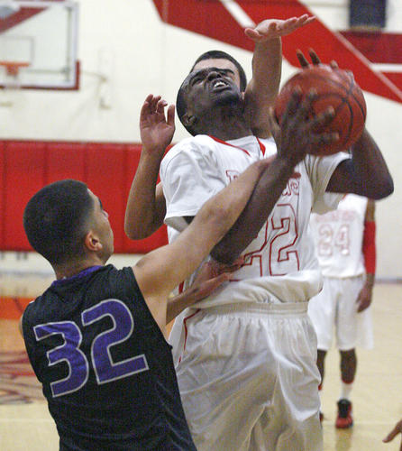 Pasadena's Hurschel Langham, at the buzzer to end the third quarter, is fouled by Hoover's Arvin Atakhanian with his teammate Teo Davidian reaching from behind to prevent a shot at Pasadena High School in a Pacific League boys basketball game at on Friday, January 4, 2013.