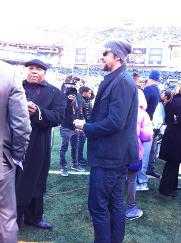 Michael Phelps, right, on the field at M&T Stadium before the playoff game with the Indianpolis Colts.